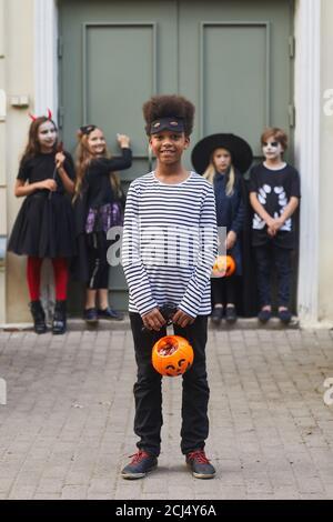 Ritratto verticale a lunghezza intera di un gruppo multietnico di bambini che indossano costumi di Halloween guardando la macchina fotografica mentre trick o trattando insieme, concentrarsi sul ragazzo afroamericano in primo piano