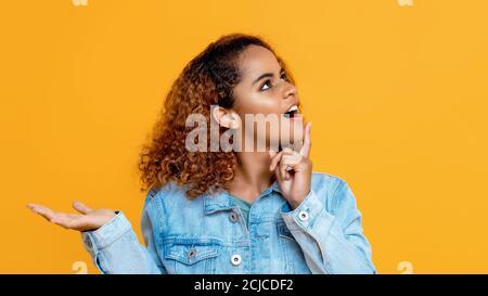 Vista laterale ritratto di pensare giovane donna afroamericana guardando su facendo gesto palmo aperto in uno sfondo giallo studio isolato Foto Stock