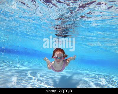 Giovane ragazza rossa testa Nuoto subacquea con occhiali in un Piscina Foto Stock