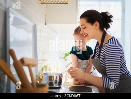 Cibo sano a casa. Famiglia felice in cucina. Madre e figlia del bambino stanno preparando il pasto adeguato.
