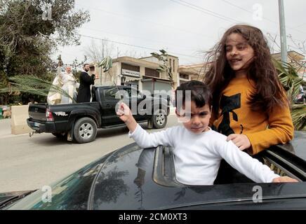 I bambini tengono rami di ulivo mentre guardano fuori dal tetto di un'automobile per essere benedetti dai sacerdoti che girano intorno ai quartieri per celebrare la Domenica delle Palme, in mezzo al blocco per contenere la malattia del coronavirus (COVID-19), a Marjayoun, Libano meridionale 5 aprile 2020. REUTERS/Aziz Taher IMMAGINI TPX DEL GIORNO