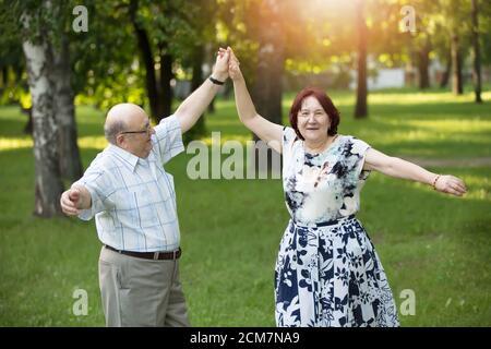 Felice anziana coppia danzante. Bei cittadini anziani, uomini e donne. Marito e moglie di vecchiaia per una passeggiata. Foto Stock