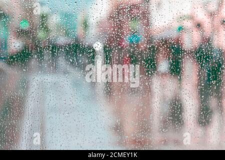 Sfondo astratto di movimento sfocato, gocce di pioggia sul vetro della finestra, la gente cammina sulla strada in giorno piovoso. Concetto di shopping, città moderna, passeggiate, stile di vita