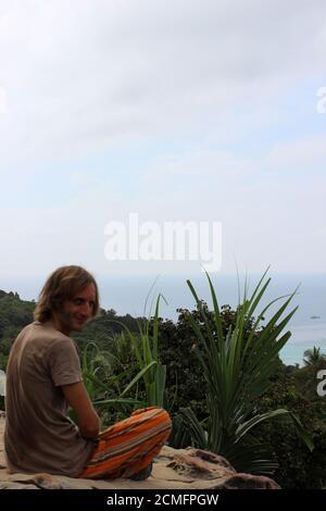 L'uomo gode di una vista sul mare. Un relax in riva al mare. Supervisione sull'orizzonte. Riposa l'atleta