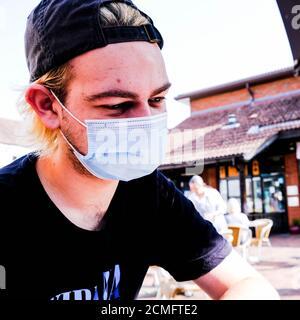 Anonymous Young Man indossa una copertura protettiva per il viso durante il COVID 19 Pandemico 2020 Foto Stock