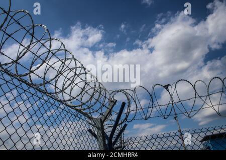 Filo spinato sulla parte superiore della rete metallica che racchiude la recinzione aeroporto contro cielo nuvoloso