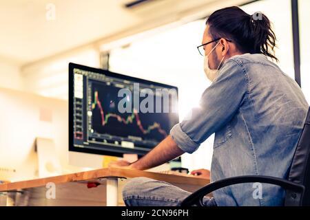 Uomo d'affari asiatico con grafico di analisi maschera facciale in nuova normalità ufficio