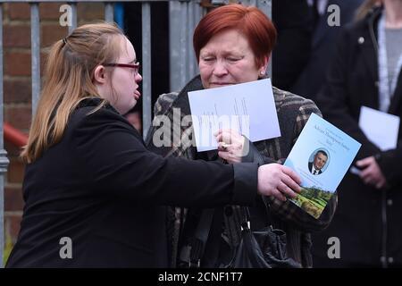 Sharon IsMay (R) è consolato da sua figlia mentre lasciano la chiesa ai funerali di suo marito, ufficiale di prigione Adrian IsMay alla Woodvale Methodist Church a Belfast, Irlanda del Nord 22 marzo 2016. IsmMay morì 11 giorni dopo l'esplosione di una bomba sotto il furgone che stava guidando. REUTERS/Clodagh Kilcoyne
