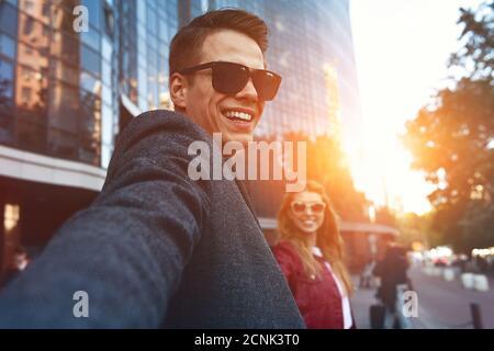 Ritratto di un giovane con borse per lo shopping in città.la gente, la vendita, l'amore e la felicità del concetto.