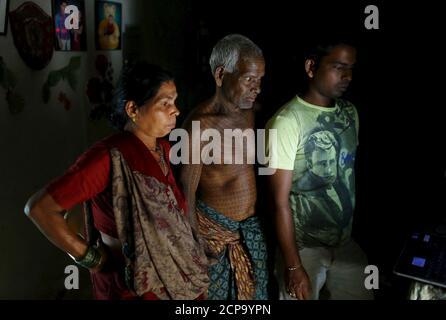 """Mahettar RAM Tandon, 76, C), seguace di Ramnami Samaj, Chi ha tatuato il nome del dio indù RAM sul suo corpo pieno, guarda un film religioso su un computer con sua moglie e figlio (R) all'interno della sua casa nel villaggio di Jamgahan, nello stato orientale di Chhattisgarh, India, 17 novembre 2015. """"È stata la mia nuova nascita il giorno in cui ho iniziato a fare i tatuaggi"""", ha detto Tandon. """"Il vecchio me era morto."""" """"La giovane generazione non si sente bravissima ad avere tatuaggi su tutto il corpo"""", ha aggiunto. 'Questo non significa che non seguano la fede.' REUTERS/ADNAN ABIDI IMMAGINE 15 DI 31 - RICERCA 'RAMNAMI' FO"""
