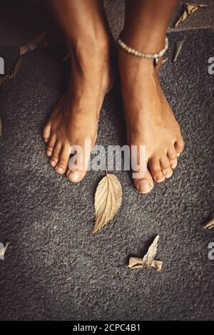 Benvenuto autunno sfondo. Closeup Concept Foto di una donna a piedi nudi piedi e foglie secche. Tema della stagione autunnale. Foto Stock