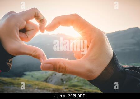 madre e figlia, donna e ragazza si uniscono a mani creando la forma del cuore con il sole che tramonta Foto Stock