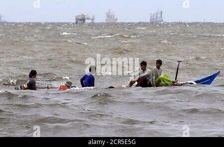 I pescatori su una piccola barca navigano lungo le onde ruvide a causa dei forti venti portati da Typhoon Goni, localmente chiamato come Ineng, in una baia di Manila nella città di Navotas, a nord di Manila 20 agosto 2015. Typhoon Goni impacchi un vento massimo sostenuto di 180 km/h vicino al centro con raffica fino a 215 km/h come il tifone ha mantenuto la sua forza che si avvicina alle province di Luzon estremo nord, l'ufficio meteorologico filippino atmosferico, Geofisico e Astronomico (PAGASA) stato riferito. REUTERS/Romeo Ranoco