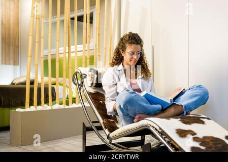 Trendy attraente donna a piedi nudi rilassante leggere un libro su un elegante e moderna sedia reclinabile a casa con un sorriso tranquillo di piacere Foto Stock