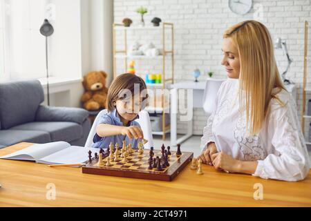 Madre e figlio giocano a scacchi al tavolo home.Happy famiglia con genitori e bambini che si divertano a giocare a tavola a casa