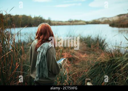 Giovane donna con il suo smartphone vicino a un lago con le cuffie Foto Stock