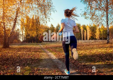 Allenamento dei corridori nel parco autunnale. Giovane donna che corre al tramonto in abiti sportivi. Stile di vita attivo. Vista posteriore