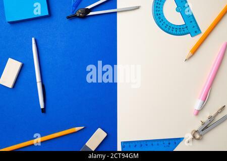 Accessori scolastici su sfondo blu e bianco vista dall'alto Foto Stock