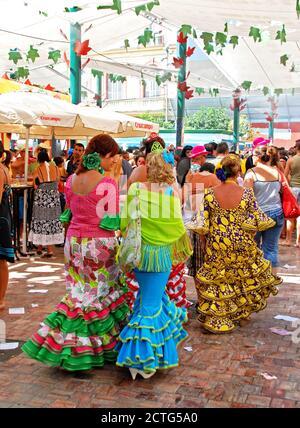 Donne in abiti flamenco lungo Calle Marques de Larios alla fiera di Malaga, Malaga, Spagna. Foto Stock