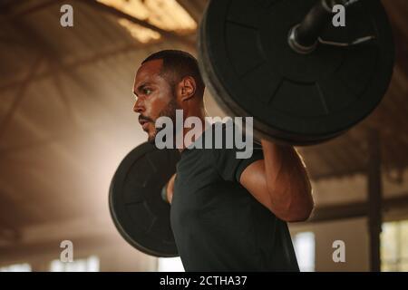 Uomo che si esercita con il barbell. Bodybuilder maschile facendo l'allenamento di sollevamento del peso in palestra cross training.