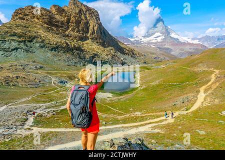 Donna escursionista zaino in spalla puntando Monte Cervino o Monte Cervino o Mont Cervin, e Alpi svizzere e Lago di Riffelsee. Attività all'aperto a Zermatt