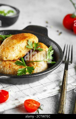 Deliziosi polpette di manzo o di pollo alla griglia. Polpettine di carne o pesce sulla padella servita con prezzemolo e pomodori. Fotografia alimentare.