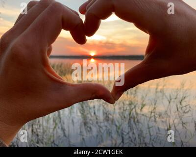 Silhouette mano a forma di cuore. Tramonto sopra il ake Foto Stock