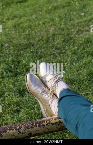 Ragazza in tuta verde e scarpe dorate. Su uno Sportsground. Primo piano delle gambe. Foto Stock