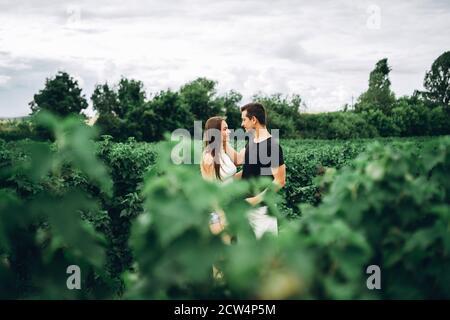 Giovane coppia amorosa, donna e uomo, abbracciando delicatamente con gli occhi chiusi sullo sfondo del campo di curry verde. Primo piano con lamelle sfocate.