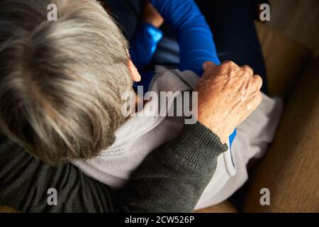 Primo piano Vista posteriore di una coppia senior amorevole a casa Abbracciando insieme il divano