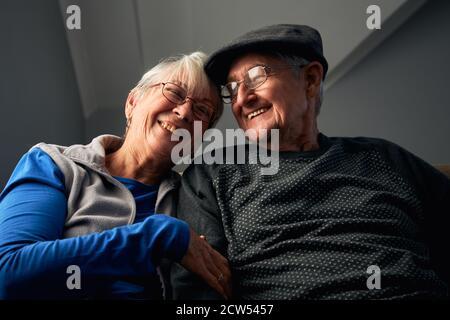 Ride Coppia anziano seduto sul divano a casa guardando la televisione Insieme