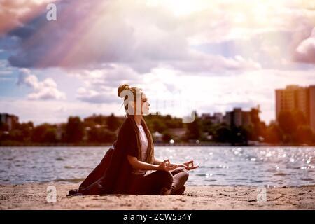 Una giovane donna con una treccia afro in abbigliamento sportivo in una posizione lotus medita sulla spiaggia. Fiume e bellissimo cielo nuvoloso. Concetto di salute e yoga. Foto Stock