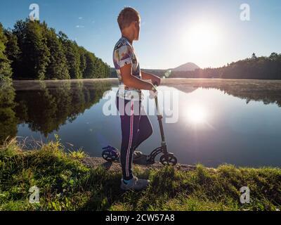 Biondo hair boy con scooter si trova su un sentiero parco lungo il lago. Concetto di sport dell'infanzia. Il sole di sera sta facendo i flares e i riflessi nell'acqua.