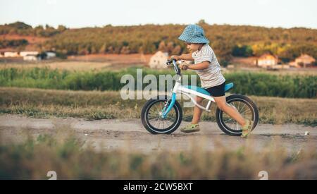 Ragazzo caucasico che cavalca la bicicletta nel cotryside indossando cappello in estate soleggiato sera