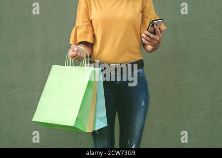 donna con borse e smartphone su sfondo verde Foto Stock