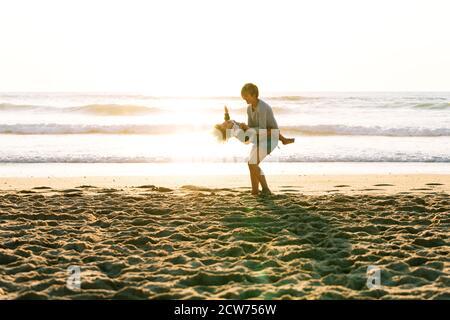 Bambino che gira tra le braccia sua madre molto felicemente sopra un tramonto in spiaggia Foto Stock