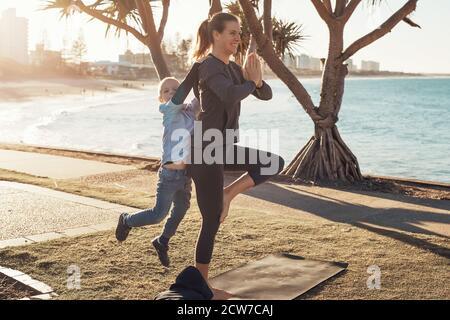 Giovane madre e figlio che fanno ginnastica e si allungano nel parco della città al sole con vista sull'oceano. Donna in asana yoga e ragazzo sulle spalle Foto Stock