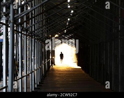 Uomo che cammina lungo il marciapiede della città sotto costruzione impalcatura con una luce brillante che si illumina sullo sfondo