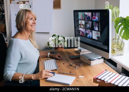 Donna matura sorridente che ha videochiamata via computer l'ufficio domestico. Videoconferenza online per riunioni di team da casa. Donna d'affari attraente