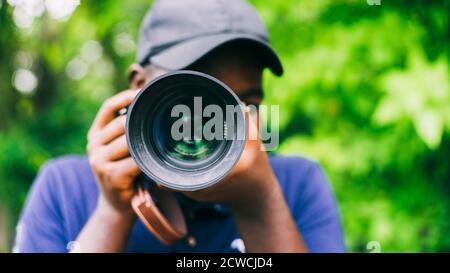 Fotografo africano uomo che prende una fotocamera.16:9 stile Foto Stock