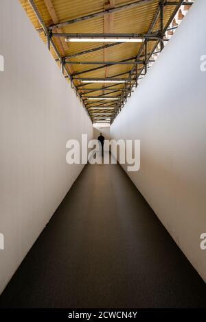 Uomo che cammina lungo un corridoio verso un'estremità ben illuminata esci