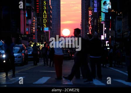 People stop to view the sunset at 42nd Street during the biannual occurrence named 'Manhattanhenge' in New York, May 29, 2013. 'Manhattanhenge', named by astrophysicist Neil deGrasse Tyson, occurs when the setting sun aligns itself with the east-west grid of streets in Manhattan, allowing the sun to shine down all streets at the same time. REUTERS/Gary Hershorn (UNITED STATES - Tags: SOCIETY ENVIRONMENT) Foto Stock