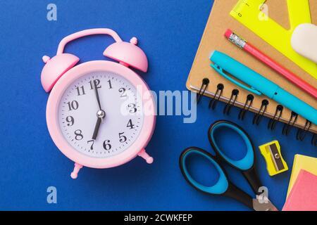 Sveglia e forniture scolastiche su sfondo blu, vista dall'alto. Concetto sul tema della preparazione alla scuola. Foto Stock