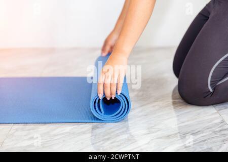 Primo piano di attraente giovane donna pieghevole yoga blu o tappetino fitness dopo l'allenamento a casa in soggiorno. La vita sana mantiene i concetti di misura.