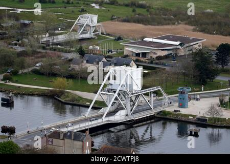 An aerial view shows Pegasus Bridge (top), the new bridge that replaced it in 1994 (bottom L) and the War Memorial in Benouville in the Normandy region, March 29, 2014. Pegasus Bridge was captured by British forces on the night of 5-6 June 1944, an important strategic point as part of the Allied invasion during World War II. France prepares to commemorate the 70th anniversary of World War II D-Day beach landings to be celebrated June 6, 2014. Picture taken March 29, 2014.    REUTERS/Christian Hartmann (FRANCE  - Tags: CONFLICT CITYSCAPE ANNIVERSARY TRAVEL) Foto Stock