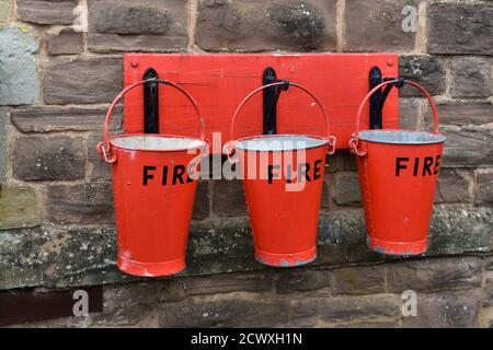 Primo piano di 3 secchi antincendio rossi appesi ai ganci su un muro di pietra all'esterno Foto Stock