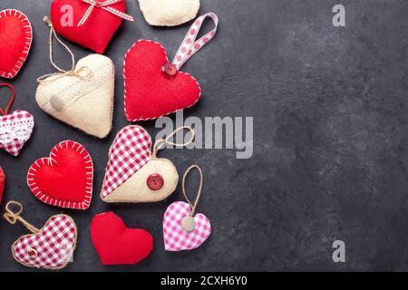 Biglietto d'auguri per San Valentino. Cuori tessili decorativi su fondo di pietra. Vista dall'alto. Spazio di copia - immagine