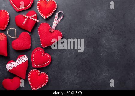 Cuori decorativi in tessuto rosso su fondo di pietra. Il concetto di San Valentino. Spazio di copia per il testo - immagine