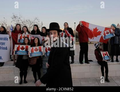 An ultra-Orthodox Jewish man walks past Israelis rallying to thank Canada's Prime Minister Stephen Harper for his support of Israel during his visit at the Israeli parliament in Jerusalem January 20, 2014. REUTERS/Ammar Awad (JERUSALEM - Tags: POLITICS)