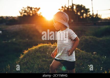 Ragazzo piccolo che gioca in un campo mentre indossa cappello e. il sole lo riscalda in una serata estiva